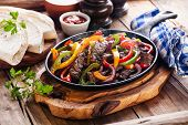 stock photo of pepper  - Beef Fajitas with colorful bell peppers in pan and tortilla bread and sauces - JPG