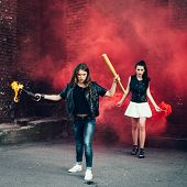 picture of teen smoking  - Two Bad fan girls with Molotov cocktail and red smoke bomb in the street - JPG