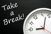 foto of breather  - The phrase Take A Break written on a blackboard next to a modern office clock - JPG