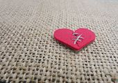 picture of broken hearted  - Red stitched broken heart on textured background - JPG