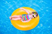 pic of girl toy  - Cute funny little toddler girl in a colorful swimming suit and sun glasses relaxing on an inflatable toy ring floating in a pool having fun during summer vacation in a tropical resort - JPG
