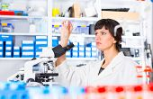 stock photo of microscope slide  - woman in a laboratory microscope with microscope slide in hand - JPG