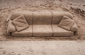 stock photo of tame  - Sand sculpture of a sofa and cushions carved out of golden beach sand on the south bank of the River Tames - JPG