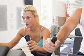 pic of exercise bike  - Close up of a fit young couple working on exercise bikes at the gym - JPG