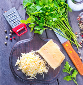 picture of grating  - grated cheese on the wooden board and on a table - JPG