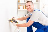 picture of  multimeter  - Electrician checking socket voltage with digital multimeter - JPG