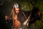 foto of werewolf  - Werewolf with a skin on his shoulder and long nails among tree branches - JPG