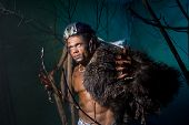 stock photo of werewolf  - Muscular man with dreadlocks and skin through the trees - JPG
