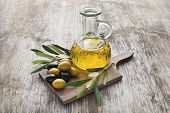 stock photo of olive branch  - Olive oil and olive branch on the wooden table - JPG