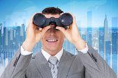 stock photo of binoculars  - Businessman holding binoculars against global business graphic in blue - JPG