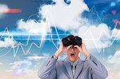 picture of binoculars  - Suprised businessman looking through binoculars against stocks and shares on black background - JPG