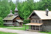 stock photo of household farm  - An old wooden house and a church in a russian village - JPG