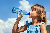 stock photo of plastic bottle  - Attractive young beautiful girl drinking water from plastic bottles - JPG
