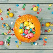 image of foreshortening  - Halloween pumpkin filled with sweets and candies over the wooden board surface - JPG
