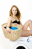 stock photo of washing machine  - Naked housewife washes clothes in a washing machine at home sitting - JPG