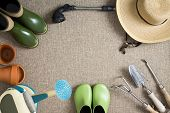 stock photo of hand tools  - Border or frame of gardening tools on a neutral beige textile background with garden shoes and boots sunhat watering can hand tools and flowerpots with central copyspace view from above - JPG