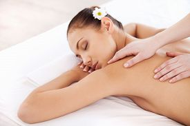 image of therapist  - Top view of attractive young woman lying on massage table and keeping eyes closed while massage therapist massaging her back - JPG