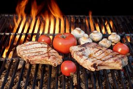 foto of braai  - Two Tasty Rib Steaks Vegetables Tomato Mushrooms Cooked Over Flaming Hot BBQ Grill - JPG