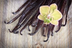 picture of vanilla  - Vanilla sticks and orchid flower on the wood background - JPG