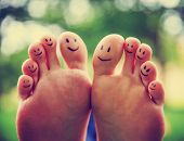 smiley faces on a pair of feet on all ten toes (VERY SHALLOW DOF - big toe on the right) in a park s poster