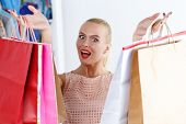 stock photo of antidepressant  - Amazed beautiful smiling woman wearing dress holding colored paper bags before her face - JPG