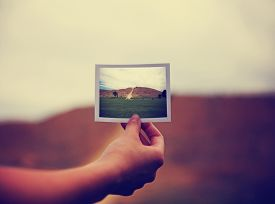 stock photo of polaroid  - a young girl holding an instant photo like a polaroid in front of a landscape that is the same but a close up instead of a wide angle toned with a retro vintage instagram filter app or action effect - JPG