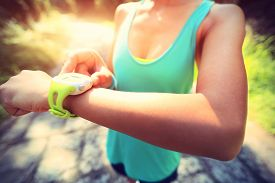 foto of jogger  - young woman jogger ready to run set and looking at sports smart watch checking performance or heart rate pulse trace - JPG