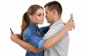 stock photo of ignore  - Portrait of young couple standing together and ignoring each other looking at smartphones - JPG