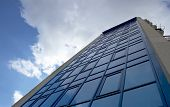 A Modern Building With Cloudy Sky poster
