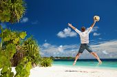 Happy man jumping on the tropical beach. White sand, blue cloudy sky and crystal sea of tropical bea poster