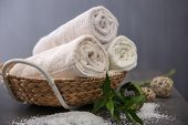 Spa towels in wicker basket on dark background poster