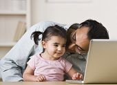 A father is holding his daughter on his lap and helping her play on the computer.  He is looking at