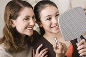 stock photo of young girls  - A beautiful young girl holding a mirror and a tube of lipstick with her mother - JPG