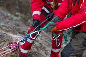 Paramedics From Mountain Rescue Service Provide First Aid During A Training For Saving A Person In A poster