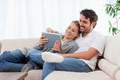 stock photo of cocoon  - In love couple using a tablet computer in their living room - JPG