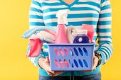 Woman In Striped Shirt Holding Box With Cleansers And Napkins On Yellow Background. Cleaning And Dis poster