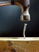 stock photo of inappropriate  - An apparent foolish attempt to hammer a screw into a piece of wood  - JPG