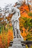 Statue Of Sensual Naked Roman Renaissance Era Woman With Flowers At Golden Autumn, Potsdam, Germany poster