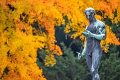 Statue Of Sensual Renaissance Era Roman Man Warrior With Sword At Golden Autumn, Potsdam, Germany poster