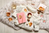 Flat Lay Composition With Book, Cup Of Tea And Warm Sweater On Fuzzy Rug poster