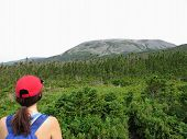 A Woman Staring Up At Gros Morne Mountain From Below.  She Is Ready To Do The Gros Morne Mountain Hi poster
