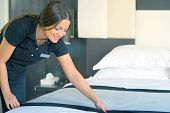 Maid Making Bed In Hotel Room. Housekeeper Making Bed. Toning poster