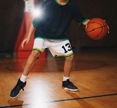 Kids Basketball Training. Young Basketball Player Dribble The Ball On The Wooden Court. Basketball T poster
