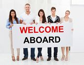 Group Of Happy People Standing Together With Welcome Aboard Placard poster