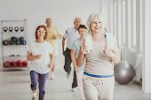 Happy Senior Woman With Towel Exercising During Fitness Classes For Elderly People poster