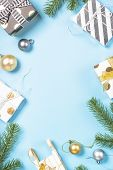 Christmas Flatlay Background. Snow Fir Tree Branch, Blue And Gold Decorations And Present Box On Blu poster