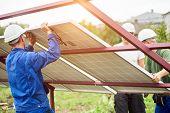 Three Professional Technicians Connecting Solar Photo Voltaic Panel To Metal Platform Using Screwdri poster