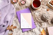 Flat Lay Composition With Notebooks, Cup Of Tea And Warm Clothes On Fuzzy Rug poster