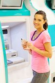 image of automatic teller machine  - happy young woman withdrawing cash at an ATM - JPG