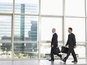 Full length of businessmen with briefcases walking in office building